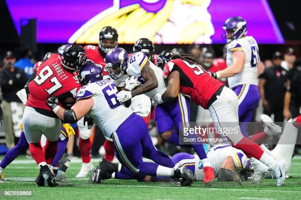 Latavius Murray of the Minnesota Vikings is tackled by Adrian Clayborn of the Atlanta Falcons at MercedesBenz Stadium on December 3 2017 in Atlanta...