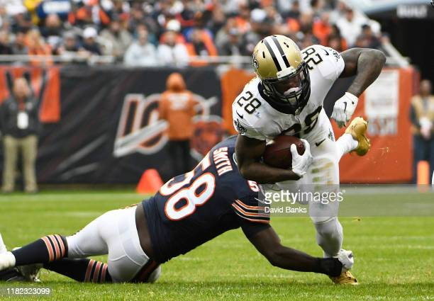 Latavius Murray of the New Orleans Saints runs the ball as Roquan Smith of the Chicago Bears tackles him during the first quarter at Soldier Field on...
