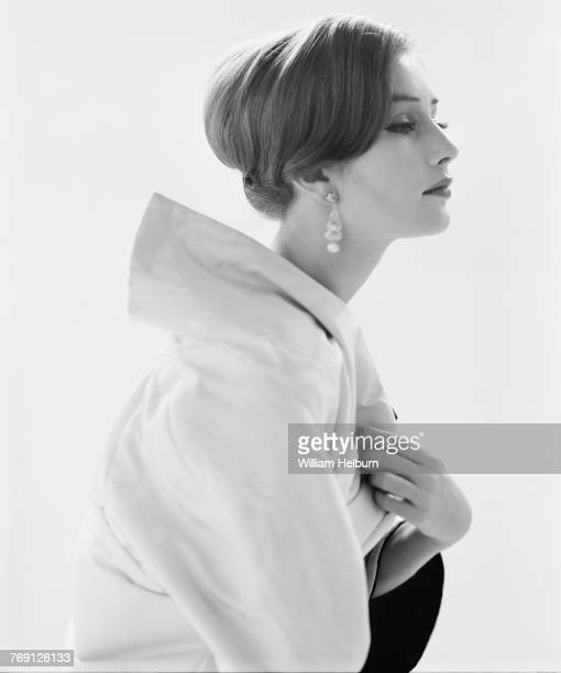Fashion model strikes an elegant pose in a white broadcollared jacket Test shot Late 1950s Black and white