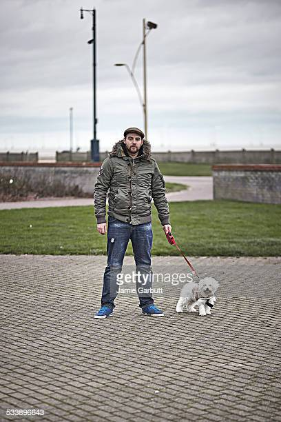 Late 20's male with dog on brick path