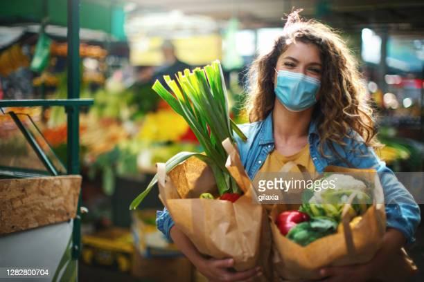 コロナウイルスのパンデミック中にビジネスが再開した後、食料品の買い物に行く20代後半の女性 - ファーマーズマーケット ストックフォトと画像