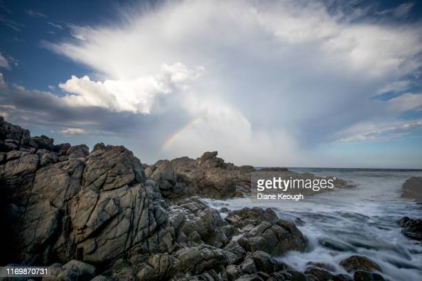 late afternoon hastings point seascape with the water coming through the rocky headland. an amazing large cloud formation with a rainbow display prior to a storm arriving. - diane hastings stock pictures, royalty-free photos & images