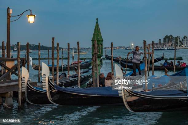 Late afternoon picture of gondolas  and some tourists aboard at San Marco, Venice Veneto Italy