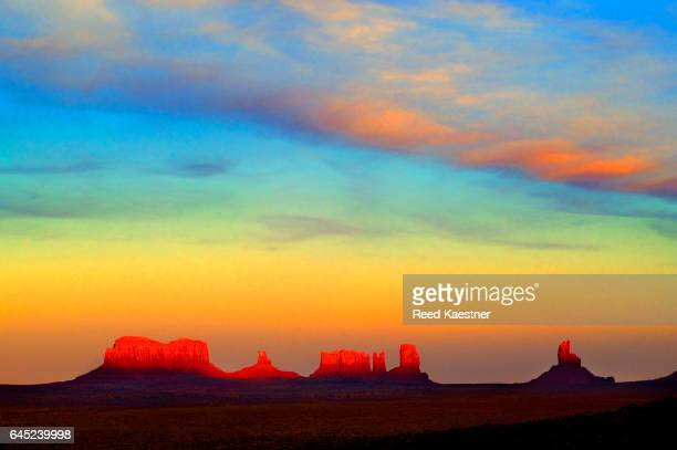 Late afternoon sun lights the sandstone bluffs at Monument Valley, in Navajo Nation