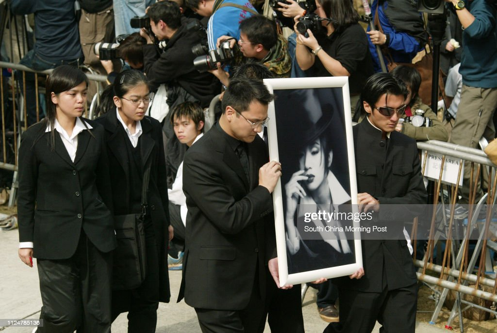 Late Anita Mui Yim-fong's nephew, Mui Pak-lun (centre), and Canto-pop star Nicholas Tse Ting-fung parade a photograph of the great artist at Cape Collinson, where she was cremated. 12 January 2004 : News Photo