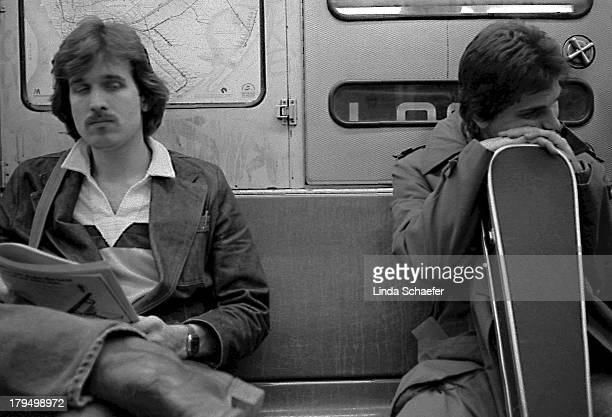 CONTENT] Late at night two travelers rest during the commute on the New York City subway One man in resting his head on his guitar case while another...