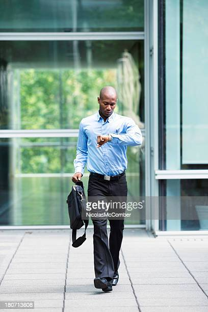 Late businessman leaving his office looking at watch