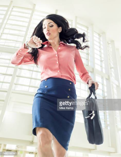 Late Caucasian businesswoman checking wristwatch