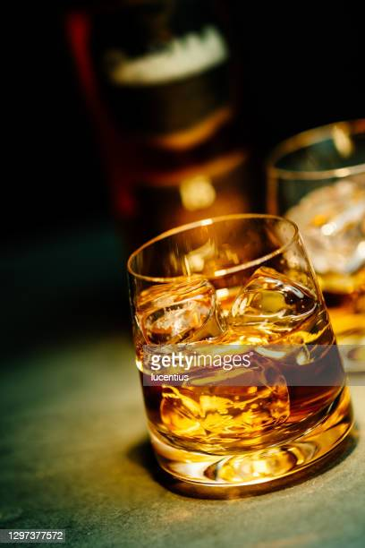 late evening glass of whiskey on ice - bourbon whiskey stock pictures, royalty-free photos & images