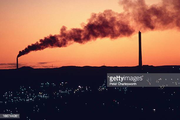 Late evening looking over Mount Isa as smoke billows from a stack from one of the mines in this small outback town Coal and iron ore are mined and...