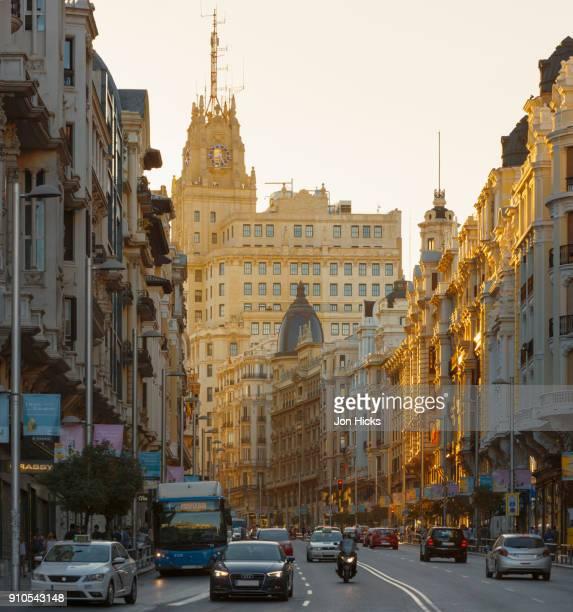 late evening sunlight falls on the gran via in central madrid. - gran via madrid fotografías e imágenes de stock