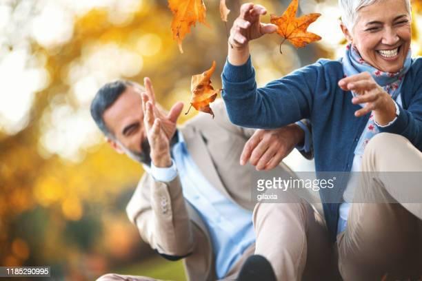 late mid adult couple having fun in a park. - gilaxia foto e immagini stock