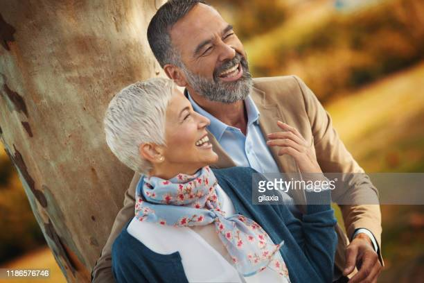 late mid adult couple having fun in a park. - mid adult stock pictures, royalty-free photos & images