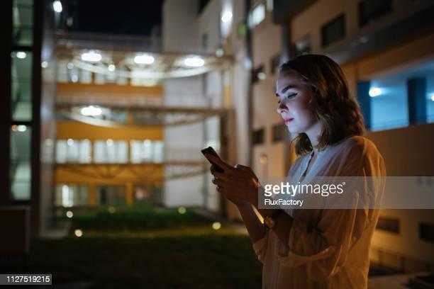 tard dans la nuit le chat sur le devant de l'immeuble de bureaux - directrice photos et images de collection