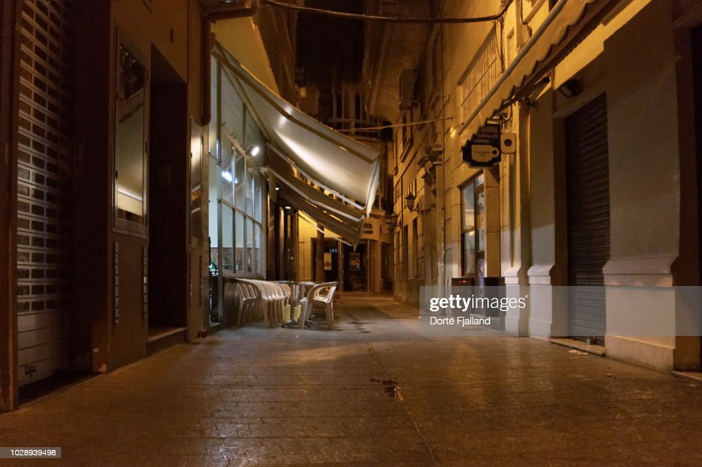 Late night/early morning view of and empty street with lights coming from a bar that is about to open for breakfast : Foto de stock
