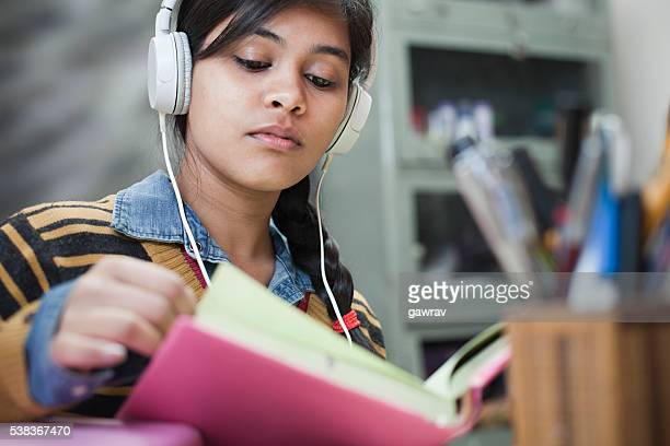 late teen girl student studying and listening music.