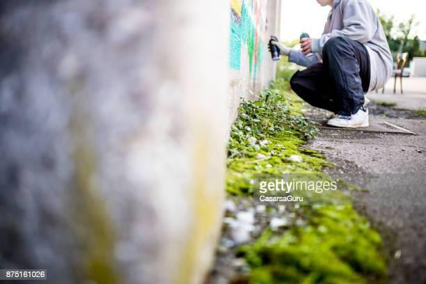 späten teenager graffiti künstler zeichnung graffiti an wand - vandalismus stock-fotos und bilder