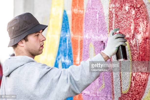 Späten Teenager Graffiti Künstler Zeichnung Graffiti an Wand