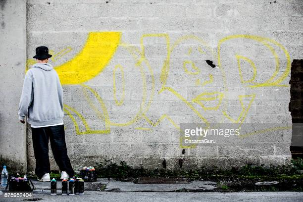late teen graffiti artist drawing graffiti on wall - baggy pants stock photos and pictures