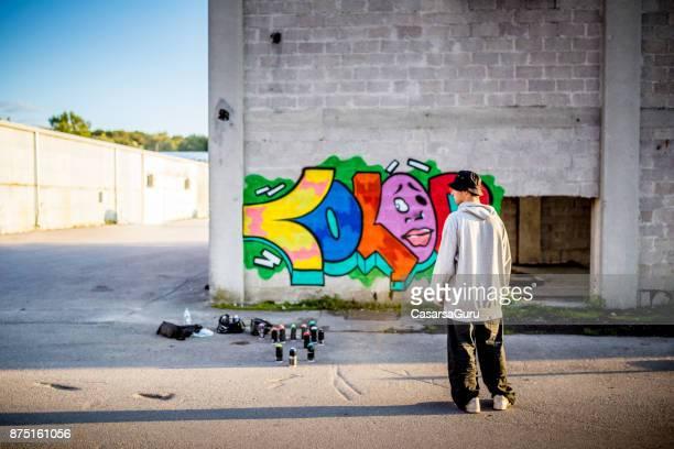 Late Teen Graffiti Artist Looking at his Graffiti