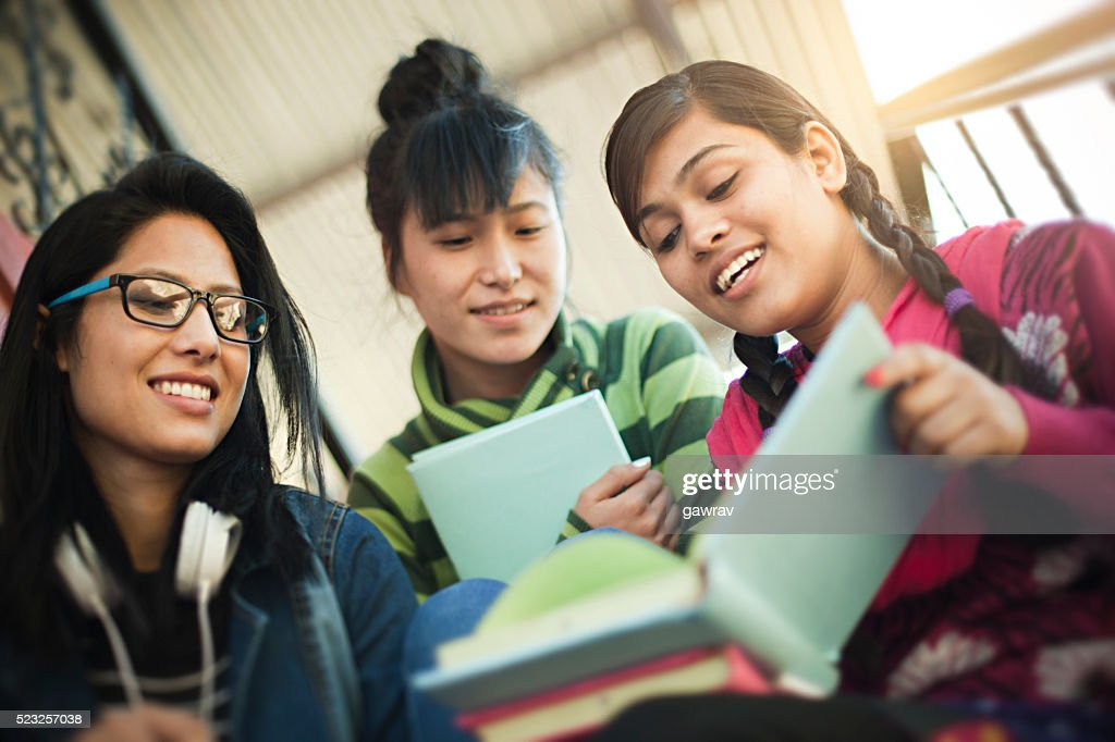 Late teen happy girl students of different ethnicity studying together. : Stock Photo