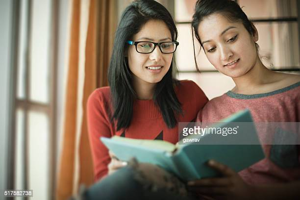 late teen happy girl students studying a book together. - indian college girls stock photos and pictures