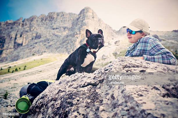 Late teen relaxing with dog at mountain pass, Dolomities