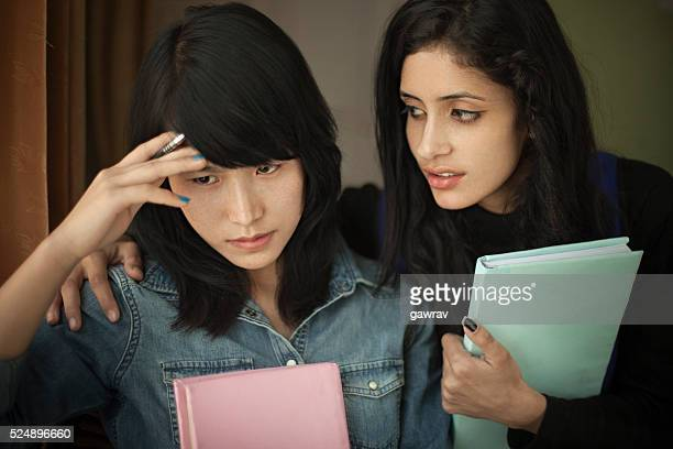 late teen student consoling to a depressed friend while studying. - hand on shoulder stock photos and pictures