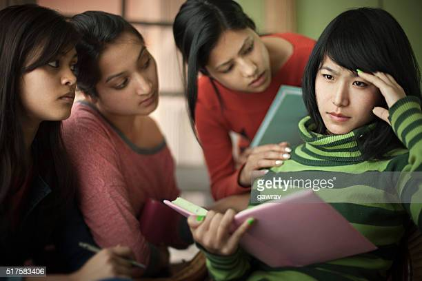 Late teen students consoling to a depressed friend while studying.