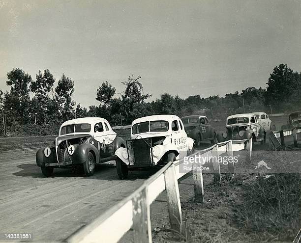 Action during a NASCAR Modified stock car race at Charlotte Speedway has Fonty Flock racing side by side with the No 14 of his brother Bob Flock