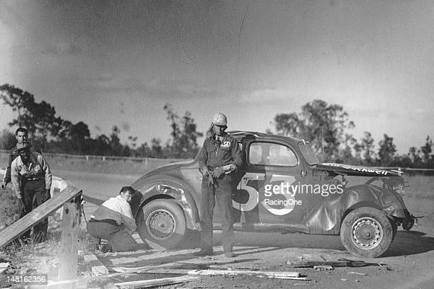 Bill Socwell overlooks the damage after he crashed his Modified stock car into a wooden guard railing during a late1940s Modified stock car race