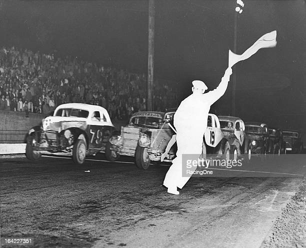 The flagman waves the green flag to start a late1940s Modified stock car race