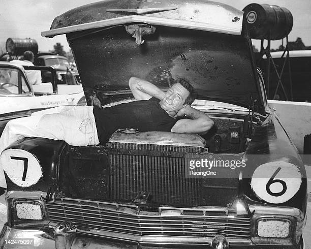 "Larry Frank finds a nice way to ""warm up"" by reclining on top of the engine in his 1956 Chevrolet NASCAR Convertible Series racer at a Convertible..."