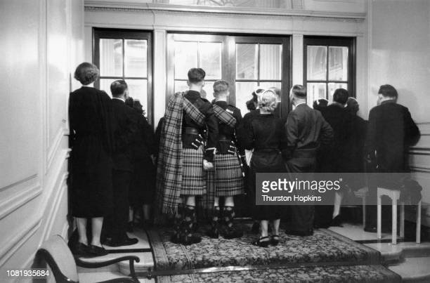 Latecomers and people without tickets crowd round the doors to watch a charity show of the new collection by French fashion designer Christian Dior...