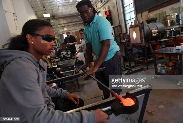 Latee Smith left helps his fellow program classmate Marco Thrasher roll hot glass in the Project Fire program on June 27 2017 in Chicago Ill Latee...