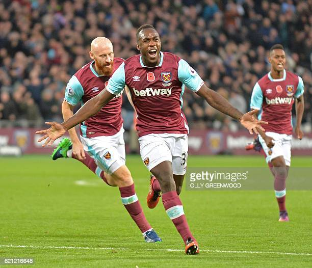 Later credited as an own goal West Ham United's English midfielder Michail Antonio celebrates after scoring the opening goal of the English Premier...