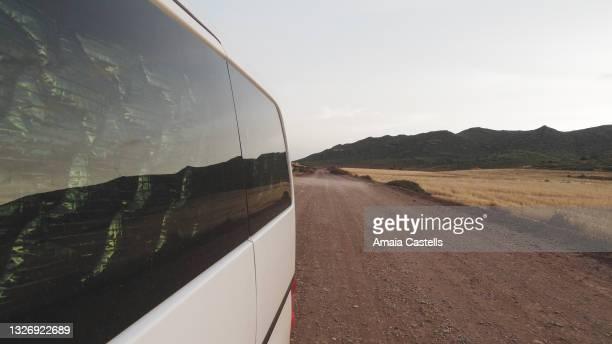 lateral de furgoneta camper circulando por camino de tierra - vista lateral stock pictures, royalty-free photos & images