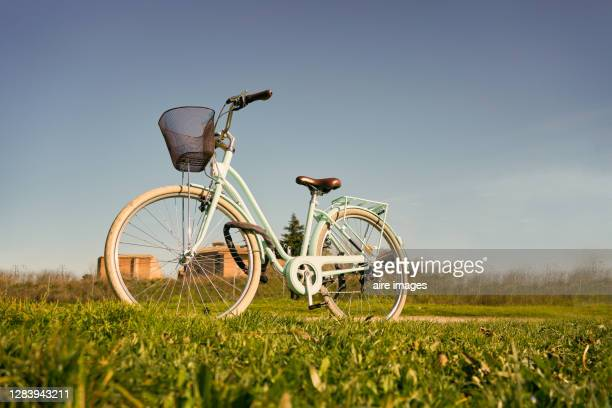 lateral view of vintage style bicycle in the countryside with blue background. stock photo - vista lateral stock pictures, royalty-free photos & images