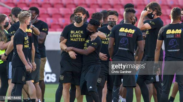 Latif Blessing of the Los Angeles FC is hugged by a team member as they meet with members of Real Salt Lake before their game was postponed at Rio...