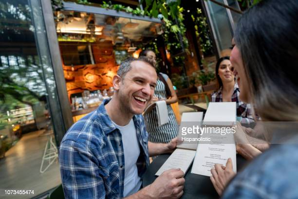latin american adult couple on a date with other friends ordering from menu while talking and laughing - funny customer service stock pictures, royalty-free photos & images