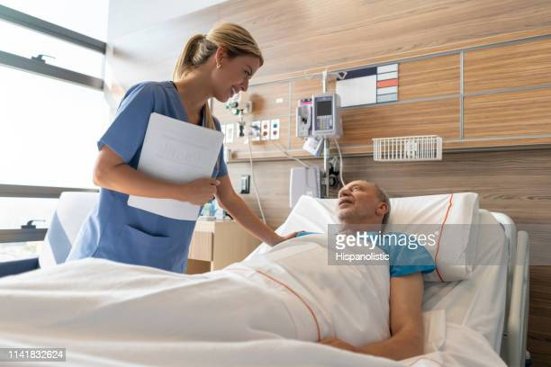 latin american beautiful doctor checking on senior patient lying down on hospital bed talking to him both smiling - cute nurses stock pictures, royalty-free photos & images