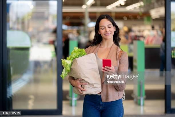 latinoamericana hermosa mujer soltera dejando el supermercado llevando comestibles en una bolsa de papel mientras charla en el teléfono inteligente muy feliz - partire fotografías e imágenes de stock