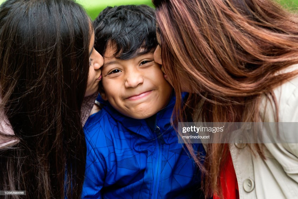Latin American boy being squezzed with love outdoors. : Stock Photo