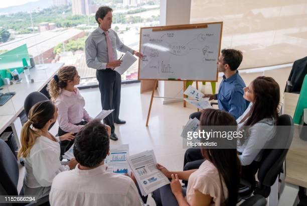 latin american business leader using a white board pointing at it explaining something to his team - hispanolistic stock photos and pictures