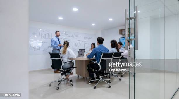 latin american business people in a meeting at the board room looking very cheerfully - hispanolistic stock photos and pictures
