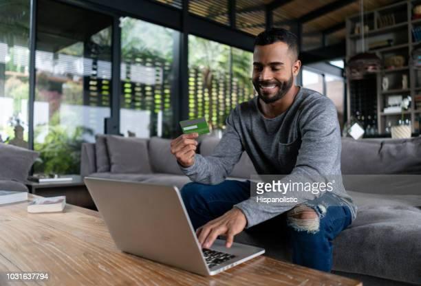 Latijns-Amerikaanse vrolijke man kopen dingen online zijn credit card bedrijf zittend op de Bank thuis