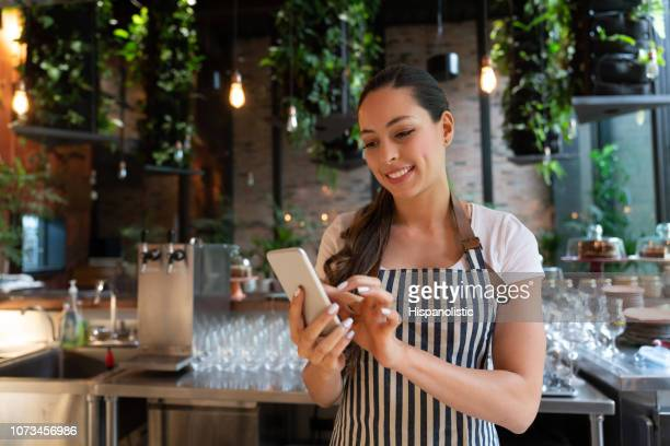 latin american cheerful waitress taking a break chatting on smartphone smiling while standing behind bar counter - happy merchant stock pictures, royalty-free photos & images