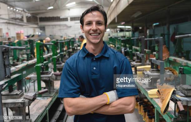 Latin american cobbler at a shoe factory facing camera with arms crossed smiling