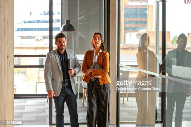 latin american colleagues, a young man and woman, at work in the office; she is showing him some data on her digital tablet. image shot in natural light; horizontal format. - colletto aperto foto e immagini stock