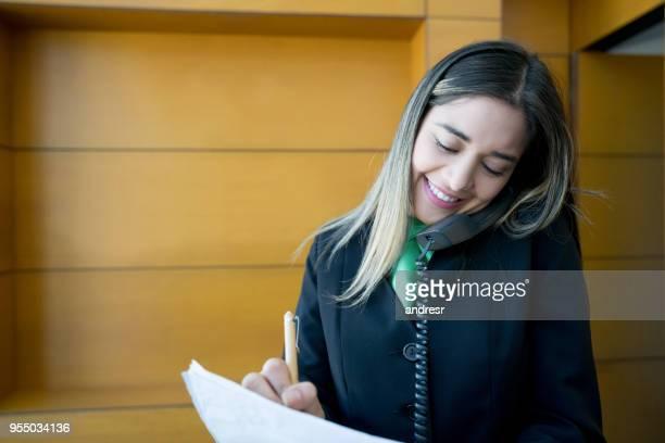 Latijns-Amerikaanse conciërge werken bij de receptie praten over de telefoon smiling